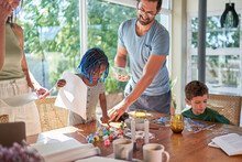 Family Painting And Assembling Jigsaw Puzzle At Home
