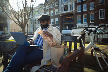 Businessman Eating Lunch And Working At Laptop In Sunny City Park