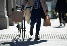 Man With. Bicycle And Grocery Bags Walking On Sunny Urban Sidewalk