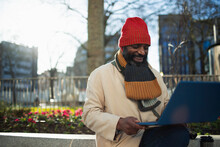 Man In Stocking Cap And Scarf Using Laptop In Sunny City Park
