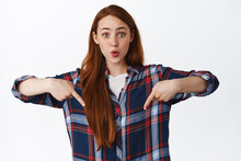 Wow Check It Out. Surprised And Curious Ginger Girl Pointing Down, Showing Advertisement Bellow With Impressed Face Expression, Standing Over White Background
