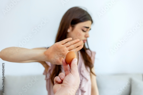 Fotografia, Obraz Pretty woman standing isolated on the white background making stop sign and refusing to eat the eggs