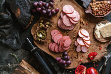 Antipasto Cold Meat Platter With Sausage, Ham, Salami, Decorated With Cheese, Fruits, Bottle Of Wine, Nuts And Olives On Wooden Board Over Black Background. Meat Appetizer, Top View