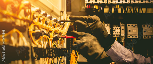 Fotografie, Obraz Electricity and electrical maintenance service, Engineer use meter checking electric current voltage at terminal block circuit breaker and cable wiring system for repair main power distribution board