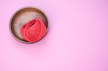 Closeup Shot Of Red Cotton Yarn On A Pink Surface - Copy Space