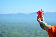 Girl Holding Flowers Over The Sky
