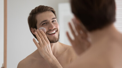 Happy handsome metrosexual guy applying sunscreen on face at mirror, spreading moisturizing collagen cream on under eye skin, reducing bags, wrinkles, protecting from sun. Male skincare concept
