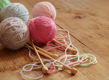 Colorful Balls Of Yarn And Knitting Needles On Wooden Background