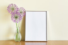 Mockup Template With A4 Frame Standing On Wooden Shelf With Three Purple Summer Flowers Branches In Glass Vase.