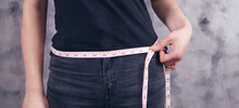 Young Girl Measures Belly With A Measuring Tape