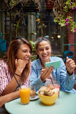 one female friend showing to another something on her cell phone in outdoor cafe