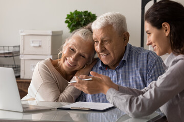 Female realtor or broker show house plan on computer to excited old middle-aged couple at meeting in office. Woman agent or consultant help mature spouses with bank loan or mortgage at briefing.
