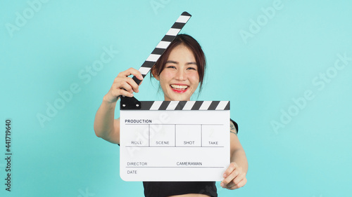 Fotografie, Obraz Asian Woman holding white clapperboard or movie clapper board on green mint or Tiffany Blue  background