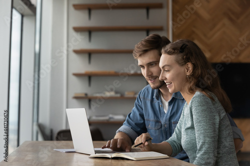 Photo Joyful young family couple using computer apps, planning future investments or web surfing information