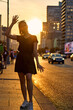 A young slim woman in the summer stands against the sun. Summer parties. An adult girl walks in the city on the streets in black clothes. Urban ordinary style.