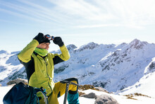 Climber Exploring Snowy Mountains In Sunny Day