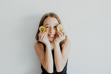Cheerful Child Covering Eyes With Kiwi Slices And Smiling