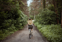 Young Girl Riding A Bicycle In The Woods