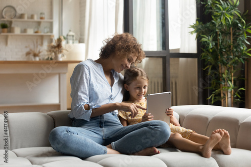 Fotografie, Obraz Relaxed carefree affectionate young mother and little preschool child daughter sitting on cozy couch, playing games on digital touchpad, spending leisure weekend time using educational applications