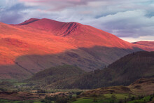 Evening Light From The Sunset Casting A Red Glow And Long Shadows On Helvellyn Mountain Range In The English Lake District.