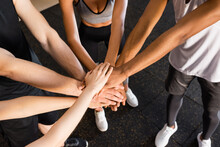 Partial View Of Young Interracial Sports People Joining Hands In Gym