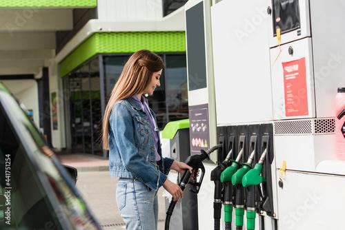 Canvastavla smiling woman taking fuel pistol on gasoline station