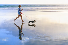 Young Happy Girl Have Fun With Dachshund Dog, Run By Water Pool Along Sea Surf On Sand Beach. Beautiful Sunset Background. Popular Travel Destination. Summer Vacation With Family Pets