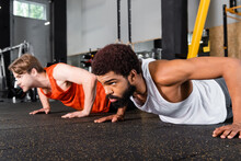 Bearded African American Man Doing Push Ups Near Blurred Sportsman