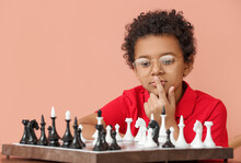 Cute African-American Boy Playing Chess On Color Background