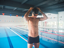 Fit Swimmer In Goggles Against Pool Before Working Out