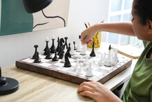 Cute African-American Boy Playing Chess At Home