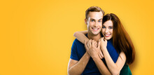 Smiling Attractive Young Amorous Couple. Embracing Caucasian Models At Happy In Love Studio Concept, Isolated On Orange Yellow Colour Background. Man And Woman Posing Together.