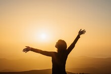 Carefree Woman Standing On Hill And Enjoying Freedom With Outstretched Arms