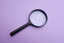 Close-up Of Magnifying Glass Against Purple Background