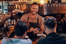 Young Bartender Serving Beer To Young Men While Standing At The Bar Counter In Pub