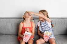 Two Little Girls Sitting On Couch Feeding Popcorn To Each Other