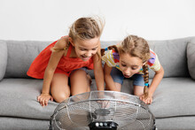 Two Funny Little Girls On Sofa Facing A Fan