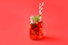 Mason Jar Of Tasty Ice Tea With Fruits On Color Background