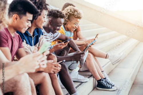 Stampa su Tela Diverse teenage students using digital smart mobile phones on college campus - G