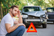 Portrait Of Upset Man Sitting On Road Near Wrecked Car After Car Accident With Red Triangle. Caucasian Scary Driver Man Sitting Near His Wrecked Car On Floor Waiting For The Insurance Service.