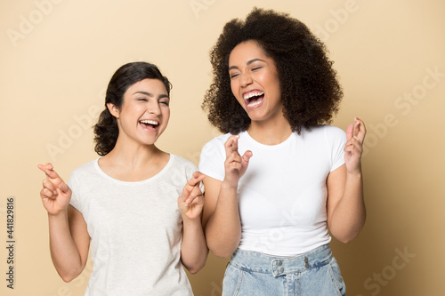 Photographie Smiling multiethnic female friends isolated on yellow studio background cross fingers laugh making wish together