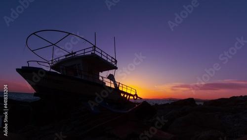 Fotografiet Fishing Boat On Beach Against Sky During Sunset