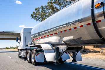 Big rig low roof profile semi truck transporting liquid cargo in shiny tank semi trailer running on the road at sunny day