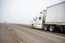 Broken White Big Rig Semi Truck With Dry Van Semi Trailer Stands On The Side Of A Foggy Road Waiting For Mobile Roadside Assistance