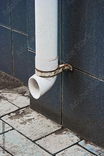 Fototapeta Plactic drainpipe on tailed wall