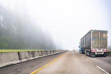 Convoy Of Big Rigs Semi Trucks With Semi Trailers Transporting Cargo Driving On The Divided Highway Road Disappearing Into The Fog Enveloping Everything Around
