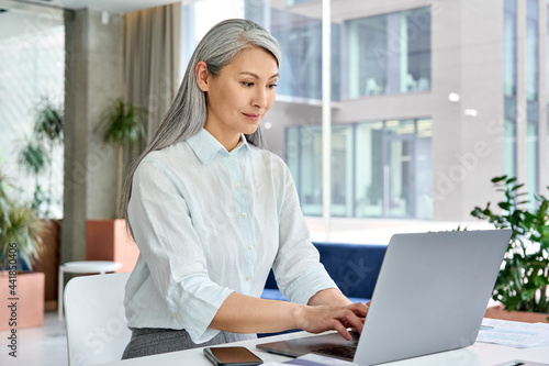 Obraz na plátně Successful confident Asian middle aged businesswoman executive top manager sitting at desk working typing on laptop computer in modern corporate office
