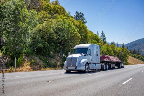 Fotografie, Obraz Powerful white big rig semi truck transporting tarped cargo on flat bed semi tra