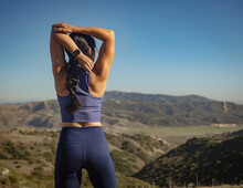 Rear View Of Woman Stretching In Landscape