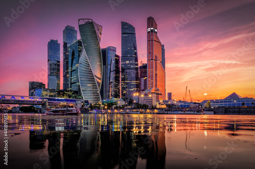 Carta da parati Illuminated Buildings By River Against Sky During Sunset